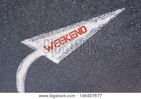 Directional White Painted Arrow With Word Weekend Over Road Surface