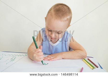 Little boy at a desk learning to draw with markers and pencils. Child with a felt-tip pen in hand. Photo with limited depth of field.