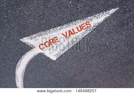 Directional White Painted Arrow With Words Core Values Over Road Surface