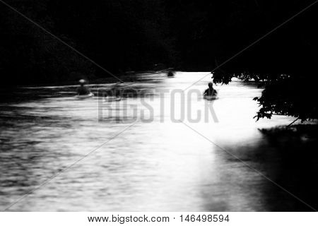 Group of canoeists on the River Avon by moonlight. Long exposure of people kayaking on river at night in black and white