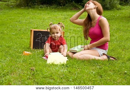 mother teaches her young children letters. they both tired