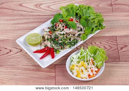 Spicy and sour mixed herb salad with pork and chicken served with side dish on wood .  Side view