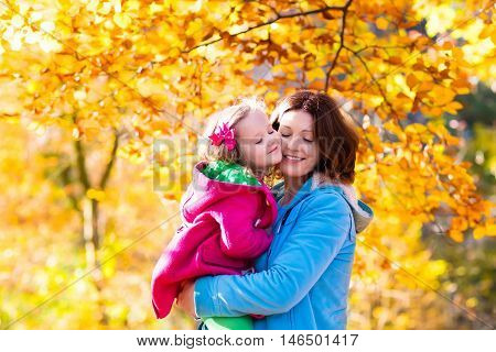 Mother and daughter play in autumn park. Parent and child walk in the forest on a sunny fall day. Children playing outdoors with yellow maple leaf. Toddler girl picking golden leaves. Mom hugging kid.