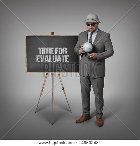 Time for evaluate text text on blackboard with businessman and globe