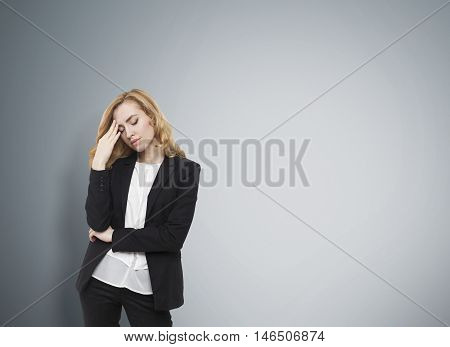 Girl in black suit standing against gray wall. She is stressed and tired. Concept of vacation needed. Mock up