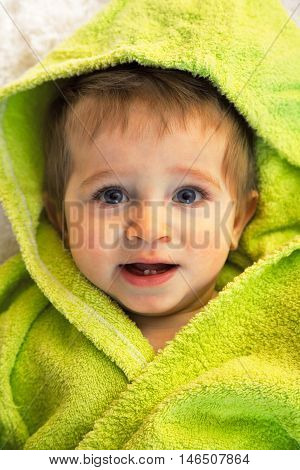 Cute boy in green bathrobe. Shot from above. Looking at the camera