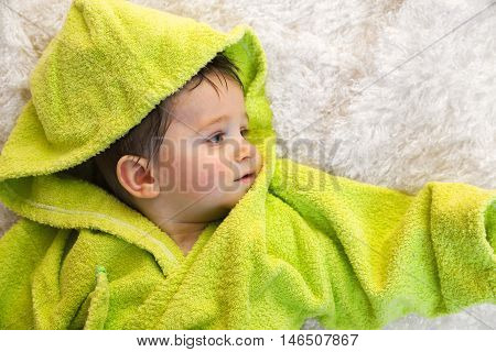 Cute boy in green bathrobe. Shot from above. Looking away from the camera