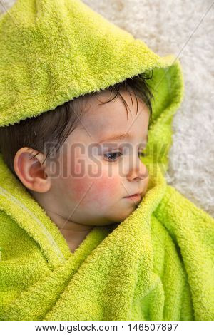 Cute boy in green bathrobe. Shot from above. Looking away from the camera. Vertical shot