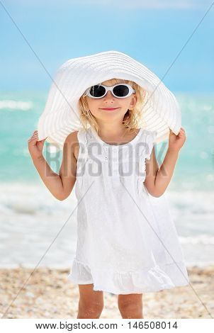 Little caucasian white girl two years old in a white dress hat and sunglasses at the beach near the sea