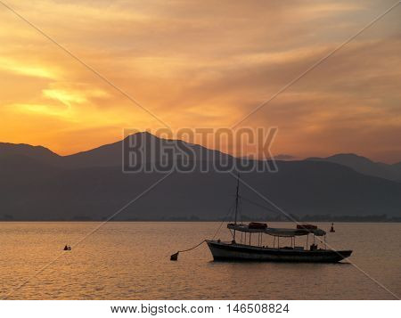 A Boat Floating on the Aegean Sea under Beautiful Golden Sky After Sunset , Nafplio, Greece
