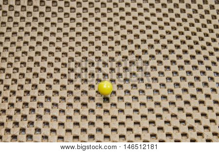 round yellow pushpin isolated on brown background