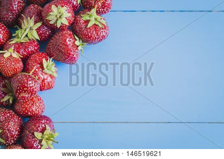 Fresh strawberries on blue wooden background, copyspase