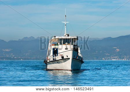 Ferry boat during navigation in front of the town of Lazise in the Garda Lake Veneto Italy. In the background the coast of Lombardy