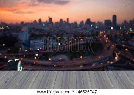 Opening wooden floor, city blurred lights aerial view with sunset background