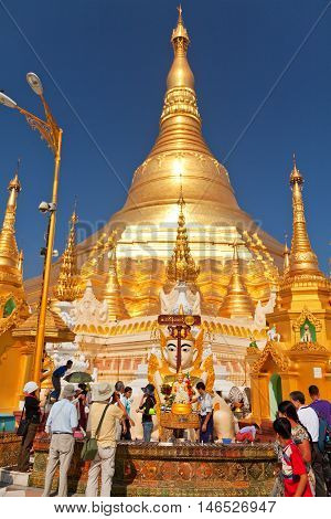 Yangon Myanmar - February 24 2011 - Tourists in front of Shwedagon Pagoda at midday