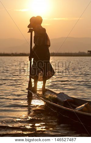 Inle Lake Myanmar - March 02 2011 - Middle aged Intha fishing from his boat at sunset
