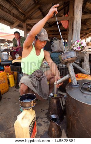 Heho Myanmar - March 02 2011 : Young Burmese man selling gasoline from a huge tank