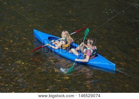 LA ROCHE-EN-ARDENNES BELGIUM - AUG 13: Girl and boy in kayak on August 14 2016 at river Ourthe near La Roche-en-Ardenne Belgium