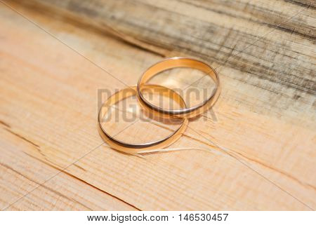 Two gold wedding rings lying on a lumber