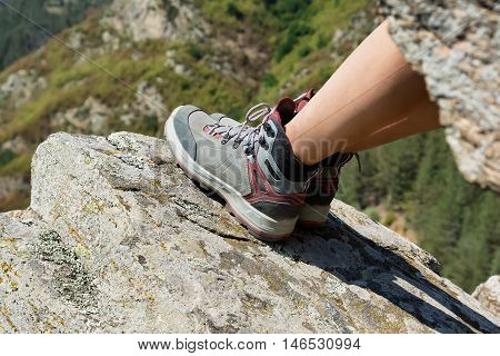 Female legs in hiking leather boots on a rocky mountain