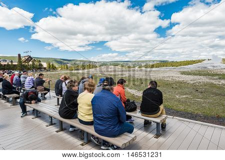 Yellowstone National Park, USA - May 17, 2016: Tired tourists sitting on benches and waiting for the eruption of Old Faithful Geyser