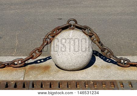 Stone ball with the iron chain lies on the road.