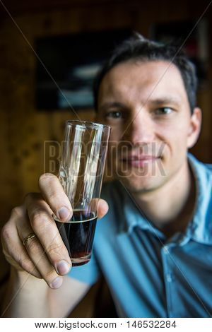 Young caucasian man holding a glass of dark stout beer for tasting