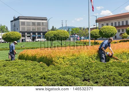 Coeur d'Alene, USA - May 3, 2016: Workers gardening and mowing shrubs by resort in downtown city