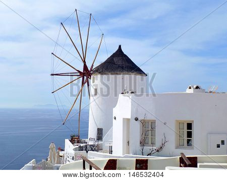 Greek Traditional Style Windmill and White Villa at Oia Village on Santorini Island, Greece