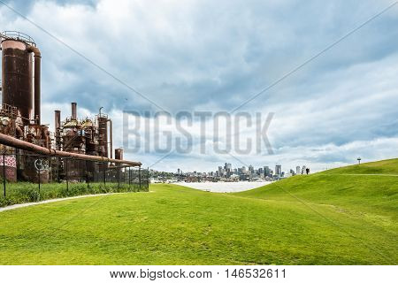 Seattle, USA - April 15, 2016: Gas Works Park and skyline or cityscape with Space Needle and People on hill with overcast, stormy sky