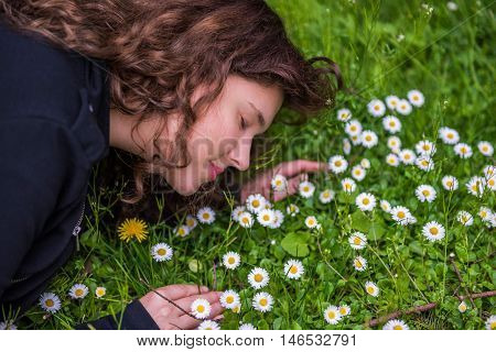 Profile portrait of young girl lying in a bed of white daisy chamomile wildflowers and dandelion smiling and smelling in grass