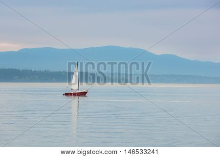 Red sailboat sailing in calm blue bay in Bellingham, Washington during purple sunset with mountain