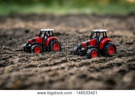 small toy tractor on the field - organic farming