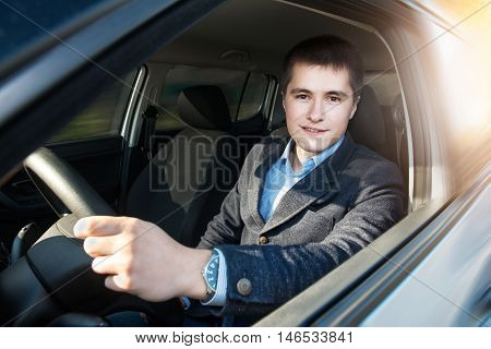 Young businessman driving a car at sunset time