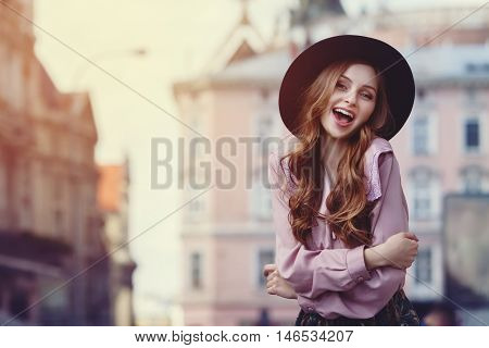 Outdoor portrait of young beautiful fashionable happy lady posing on a street of the old city. Model wearing stylish wide-brimmed hat and clothes. Girl looking at camera. Female fashion. City lifestyle.