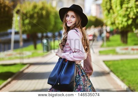 Outdoor portrait of young beautiful fashionable happy smiling lady walking on street of the old city. Model wearing stylish fedora hat and clothes. Girl looking at camera. Female fashion. City lifestyle