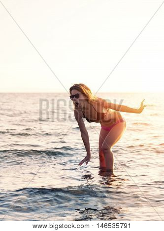 Young woman stepping on something in the shallow water