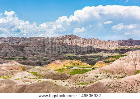 Landscape view of Badlands National Park with green plants and curved road with cars and clouds