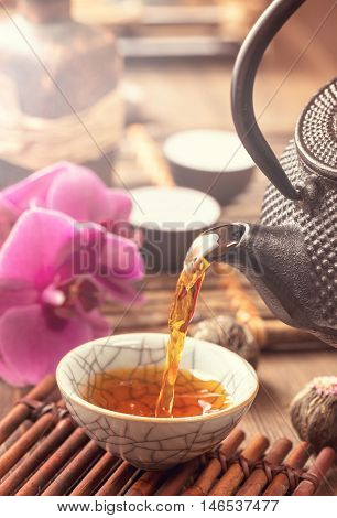 Pouring black tea into traditional oriental cup.Toned. Closeup
