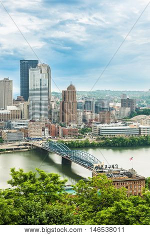 Pittsburgh, USA - June 3, 2016: Vertical view of city cityscape or skyline with dark storm clouds, Smithfield street bridge and Monongahela river