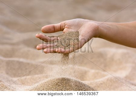 sand running through hand of woman on the beach background