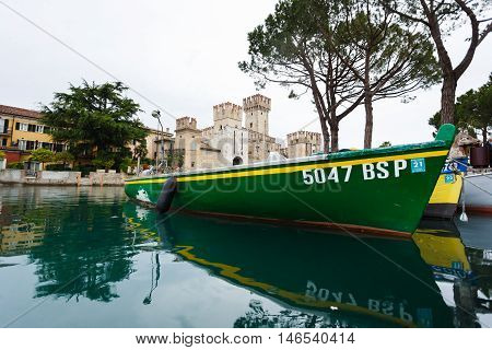 Sirmione Italy - May 09 2016: Castle of Scaligero with a boat on the foreground at rainy weather