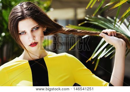 Outdoor portrait of young beautiful fashionable lady posing on the street. Model wearing stylish yellow summer dress. Girl looking at camera. Female fashion concept. City lifestyle. Sunny day. Close up.
