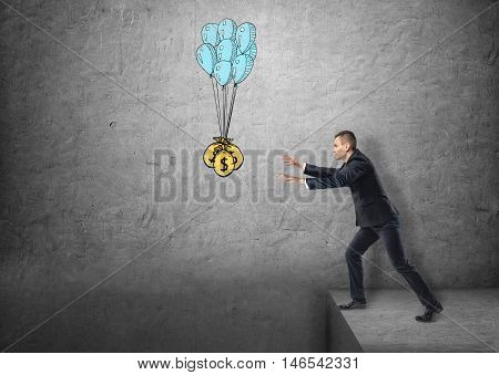 Businessman standing on the edge reaching for sacks of money hanged on balloons. Lust of money. Eagerness and zeal. Money-grubbing.