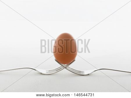 egg in balance on two forks with white wooden kitchen table and space for text. whit background