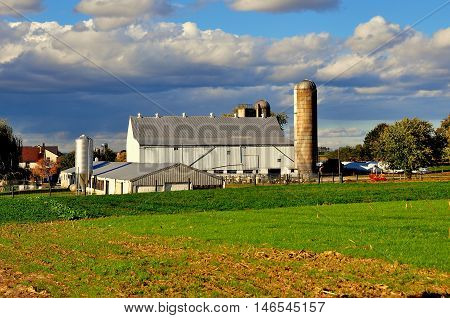 Lancaster County Pennsylvania - October 17 2015: A pristine Amish farm with large barn, silos, and surrounding fields