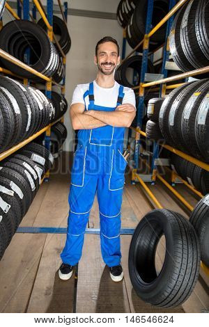 Mechanic standing between car tires in tire store