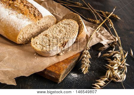 Fragrant fresh-baked rye bread on a black wooden table. Bread is sliced. Spikelets of wheat and rye close. Rustic Style. Close view
