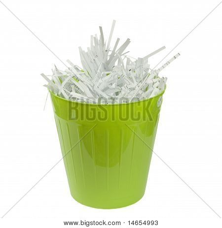 green wastebasket with shredded paper