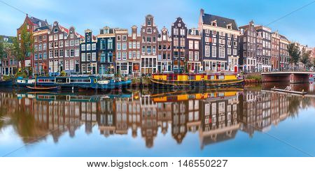 Panorama of Amsterdam canal Singel with typical dutch houses and houseboats during morning blue hour, Holland, Netherlands.